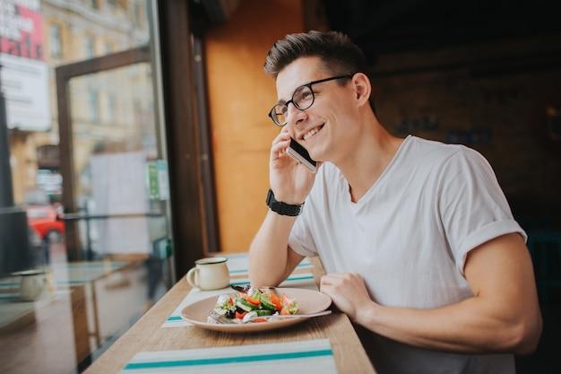 Il giovane uomo caucasico che mangia un'insalata sana e parla per telefono