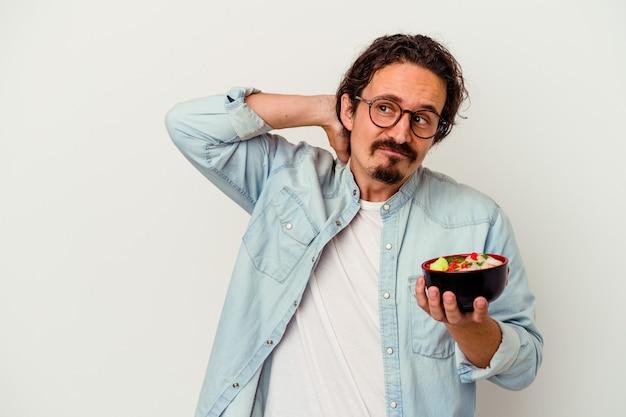 Giovane uomo caucasico che mangia un ramen che tocca la parte posteriore della testa, pensando e facendo una scelta.