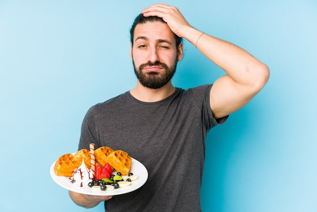 Giovane uomo caucasico che mangia un dessert della cialda isolato essendo scioccato, ha ricordato un incontro importante.