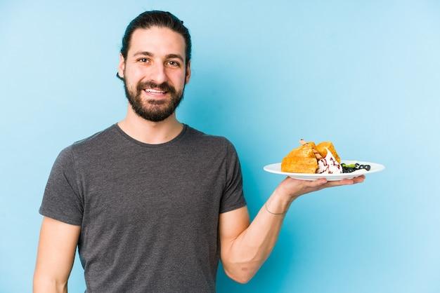 Giovane uomo caucasico che mangia un dessert della cialda isolato che mostra uno spazio della copia su una palma e che tiene un'altra mano sulla vita.