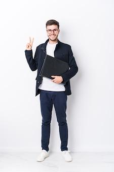 Corpo pieno del giovane uomo caucasico isolato che mostra il numero due con le dita.