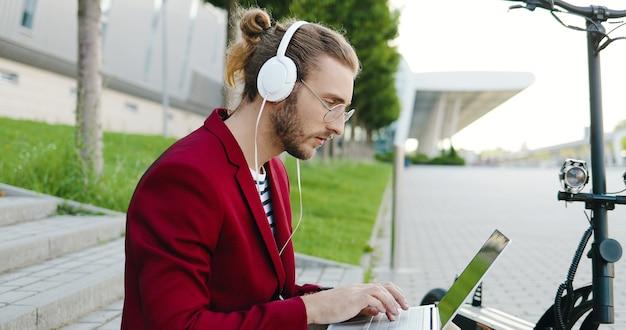 Giovane uomo caucasico in occhiali e cuffie seduto sui gradini all'aperto, lavorando su un computer portatile, digitando sulla tastiera. un ragazzo elegante lavora in strada come libero professionista. scooter elettrico. ascoltare la musica.