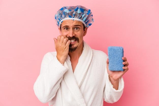 Giovane uomo caucasico che va alla doccia tenendo una spugna isolata su sfondo rosa che si morde le unghie, nervoso e molto ansioso.