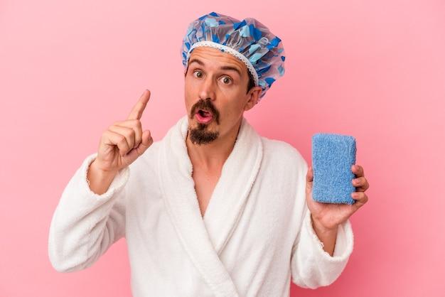 Giovane uomo caucasico che va alla doccia tenendo la spugna isolata su sfondo rosa con un'idea, un concetto di ispirazione.