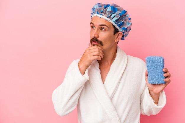 Giovane uomo caucasico che va alla doccia tenendo la spugna isolata su sfondo rosa guardando lateralmente con espressione dubbiosa e scettica.