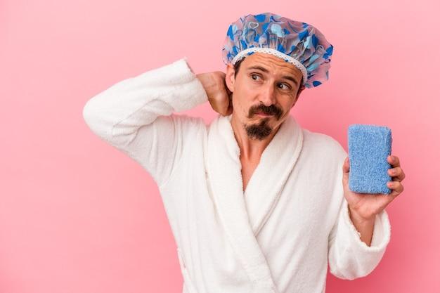 Giovane uomo caucasico che va alla doccia tenendo la spugna isolata su sfondo rosa toccando la parte posteriore della testa, pensando e facendo una scelta.