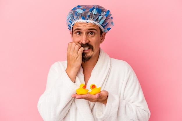Giovane uomo caucasico che va sotto la doccia con anatre di gomma isolate su sfondo rosa che si mordono le unghie, nervoso e molto ansioso.