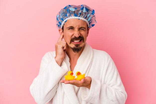 Giovane uomo caucasico che va sotto la doccia con anatre di gomma isolate su sfondo rosa che copre le orecchie con le mani.