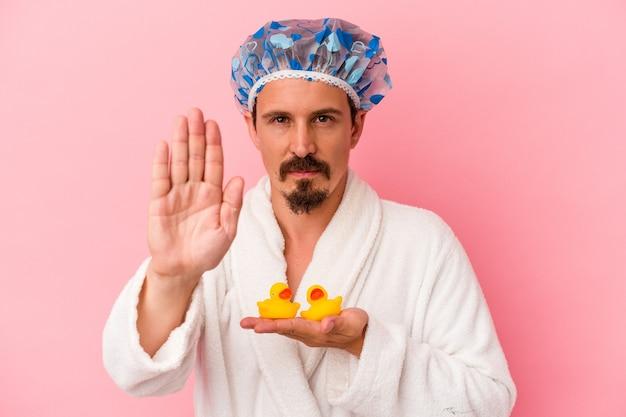 Giovane uomo caucasico che va alla doccia con anatre di gomma isolate su sfondo rosa in piedi con la mano tesa che mostra il segnale di stop, impedendoti.