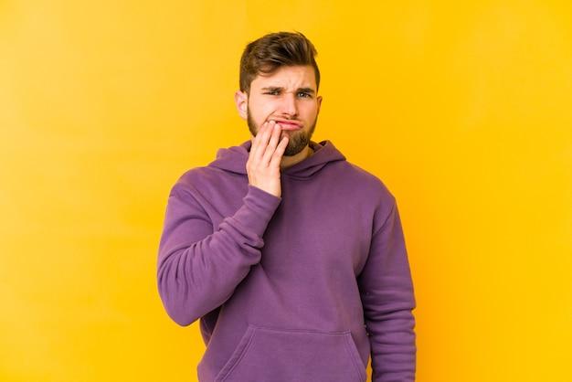Giovane uomo caucasico che ha un forte dolore ai denti, dolore molare.