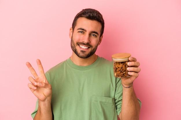 Giovane uomo caucasico che tiene un barattolo di mandorle isolato sulla parete rosa che mostra il numero due con le dita.