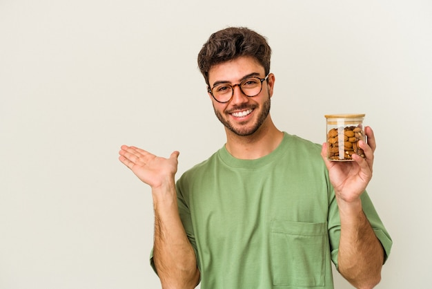 Giovane uomo caucasico che tiene un barattolo di mandorle isolato su sfondo bianco che mostra uno spazio di copia su un palmo e tiene un'altra mano sulla vita.
