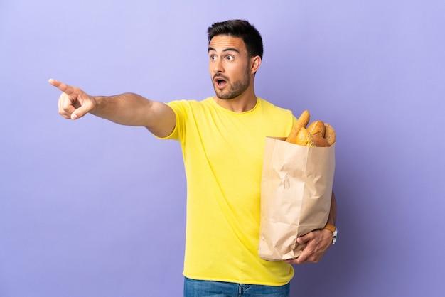 Giovane uomo caucasico che tiene un sacchetto pieno di pane isolato su sfondo viola che punta lontano