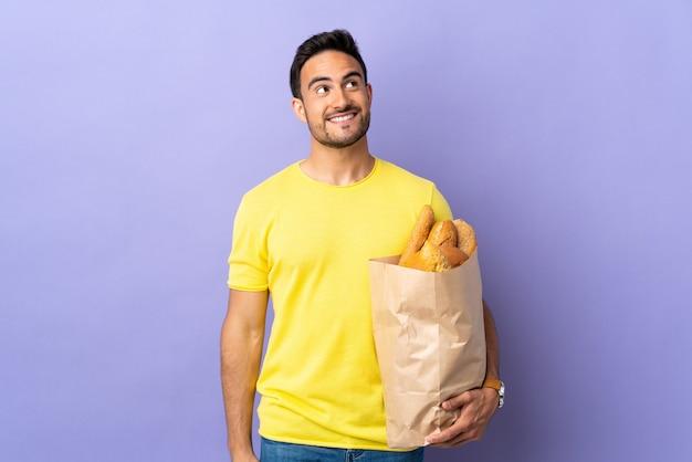 Giovane uomo caucasico che tiene una borsa piena di pane isolato su viola ridendo e guardando in alto