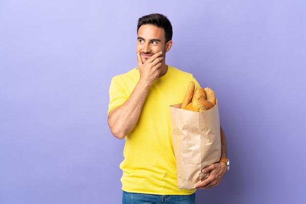 Giovane uomo caucasico che tiene una borsa piena di pane isolato su viola pensando un'idea