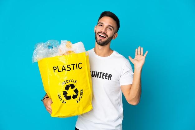 Giovane uomo caucasico tenendo un sacchetto pieno di bottiglie di plastica da riciclare isolato su sfondo blu salutando con la mano con felice espressione