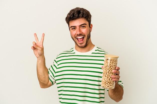 Giovane uomo caucasico che tiene barattolo di ceci isolato su sfondo bianco gioioso e spensierato che mostra un simbolo di pace con le dita.