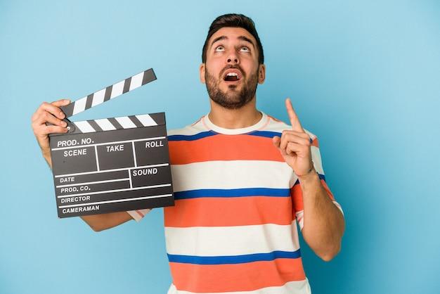 Giovane uomo caucasico tenendo un ciak isolato su sfondo blu rivolto verso l'alto con la bocca aperta.
