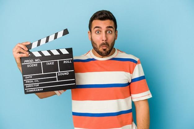 Giovane uomo caucasico che tiene un ciak isolato su sfondo blu alza le spalle e gli occhi aperti confusi.