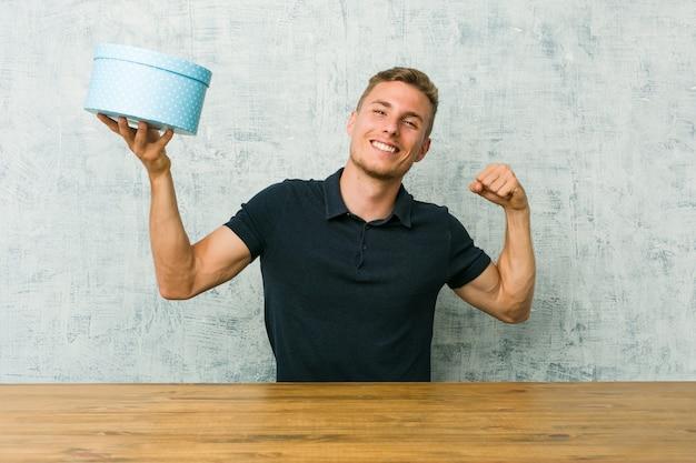 Giovane uomo caucasico che tiene una confezione regalo su un tavolo che mostra il gesto di forza con le braccia, simbolo del potere femminile