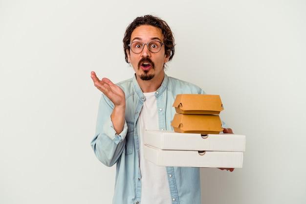 Giovane uomo caucasico tenendo hamburger un pizze isolati su sfondo bianco sorpreso e scioccato.