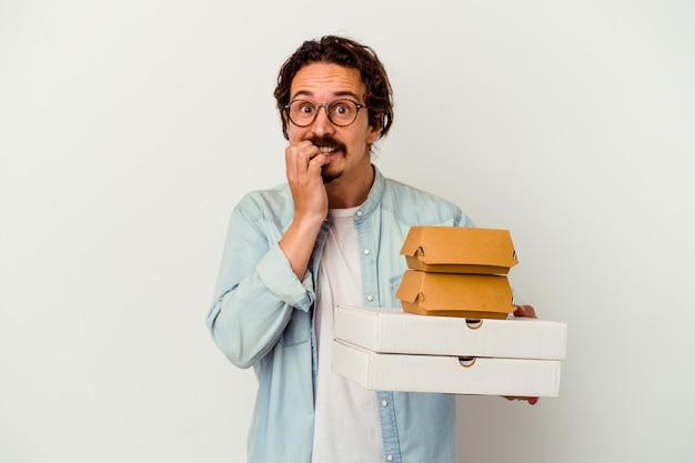 Giovane uomo caucasico che tiene hamburger e pizze isolate su unghie mordaci bianche, nervose e molto ansiose.