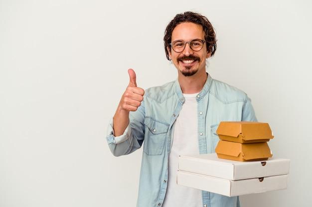 Giovane uomo caucasico che tiene hamburger e pizze isolate su bianco sorridendo e alzando il pollice