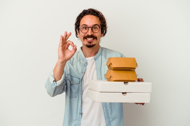 Giovane uomo caucasico che tiene hamburger e pizze isolate sul muro bianco allegro e fiducioso che mostra gesto giusto