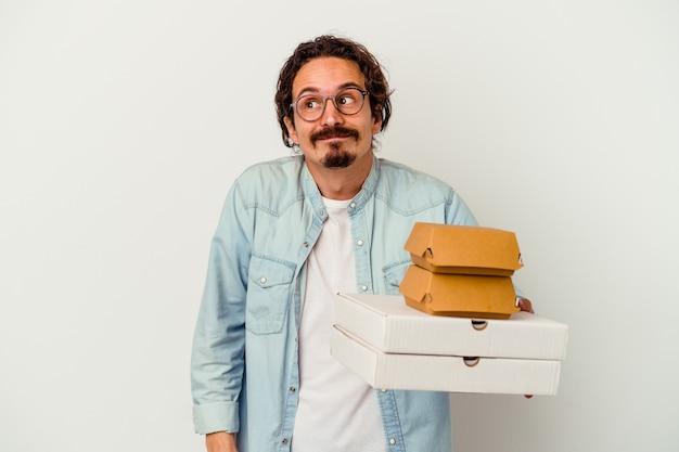 Giovane uomo caucasico che tiene hamburger e pizze isolate sul muro bianco sognando di raggiungere obiettivi e scopi