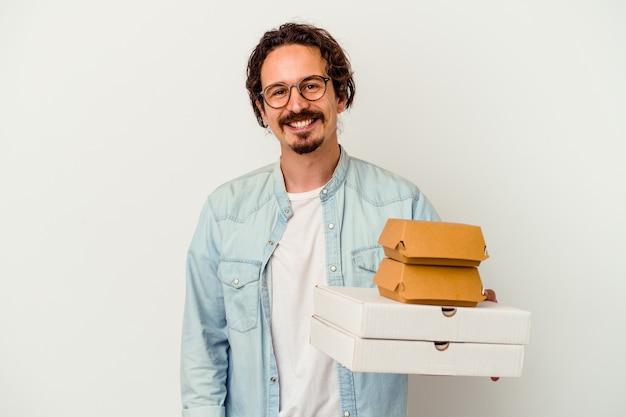 Giovane uomo caucasico che tiene hamburger e pizze isolate sul muro bianco felice, sorridente e allegro.
