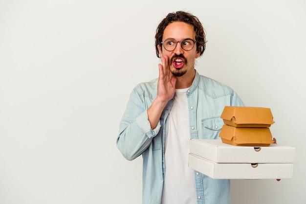 Il giovane uomo caucasico che tiene hamburger e pizze isolate sul muro bianco sta dicendo una notizia segreta di frenata calda e sta guardando da parte
