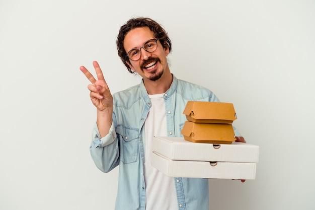 Giovane uomo caucasico che tiene hamburger e pizze isolate sul muro bianco gioioso e spensierato che mostra un simbolo di pace con le dita