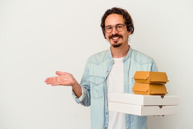 Giovane uomo caucasico che tiene hamburger e pizze isolate sulla parete bianca che mostra uno spazio della copia su una palma e che tiene un'altra mano sulla vita