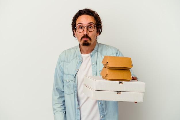 Giovane uomo caucasico che tiene hamburger e pizze isolate sul muro bianco alza le spalle e gli occhi aperti confusi