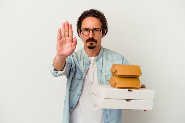 Giovane uomo caucasico che tiene hamburger e pizze isolate sul muro bianco in piedi con la mano tesa che mostra il segnale di stop, impedendoti.