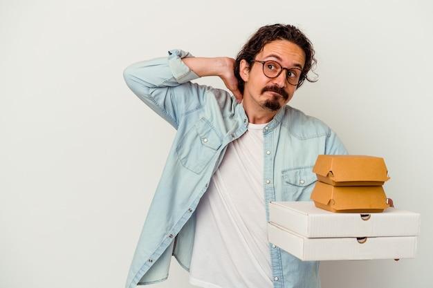 Giovane uomo caucasico che tiene hamburger e pizze isolate sulla parete bianca che tocca la parte posteriore della testa, pensando e facendo una scelta