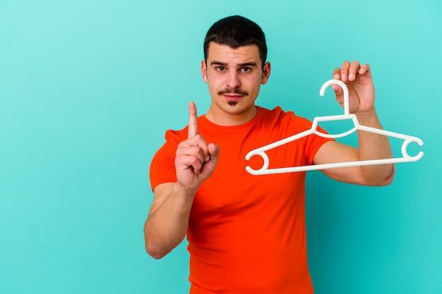 Giovane uomo caucasico che tiene un gancio isolato su sfondo blu che mostra il numero uno con il dito.