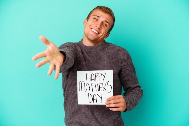 Giovane uomo caucasico che tiene una felice festa della mamma isolata su blue