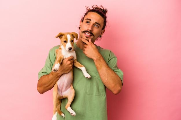 Giovane uomo caucasico che tiene il suo cucciolo isolato su sfondo rosa