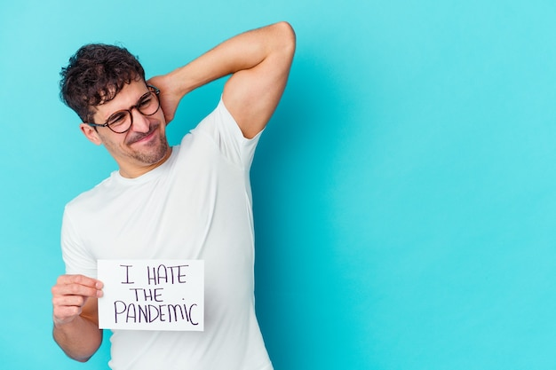 Giovane uomo caucasico che tiene un io odio il cartello pandemico isolato toccando la parte posteriore della testa, pensando e facendo una scelta