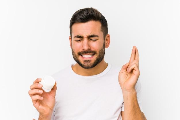 Il giovane uomo caucasico che tiene una crema idratante ha isolato le dita incrociate per avere fortuna