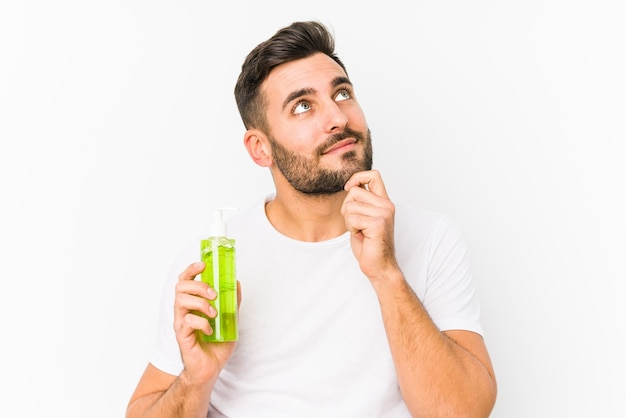 Giovane uomo caucasico che tiene una crema idratante con aloe vera isolato guardando lateralmente con espressione dubbiosa e scettica.