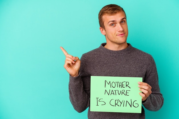 Il giovane uomo caucasico che tiene una madre natura sta piangendo cartello isolato sulla parete blu che sorride allegramente indicando con l'indice lontano.