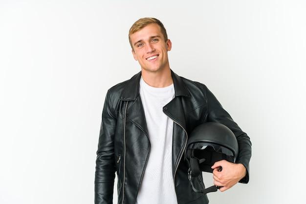 Il giovane uomo caucasico che tiene un casco della motocicletta isolato su priorità bassa bianca si sente orgoglioso e sicuro di sé, esempio da seguire.