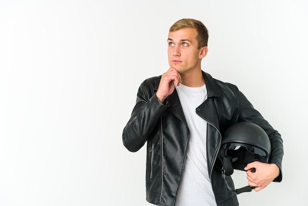 Giovane uomo caucasico che tiene un casco da motocicletta isolato sul muro bianco che guarda lateralmente con espressione dubbiosa e scettica.