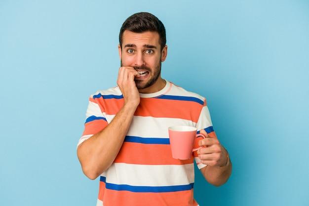 Giovane uomo caucasico che tiene una tazza isolata sulle unghie mordaci del fondo blu, nervoso e molto ansioso.