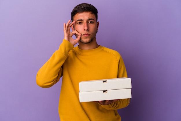 Giovane uomo caucasico che tiene le pizze isolate su sfondo viola con le dita sulle labbra mantenendo un segreto.