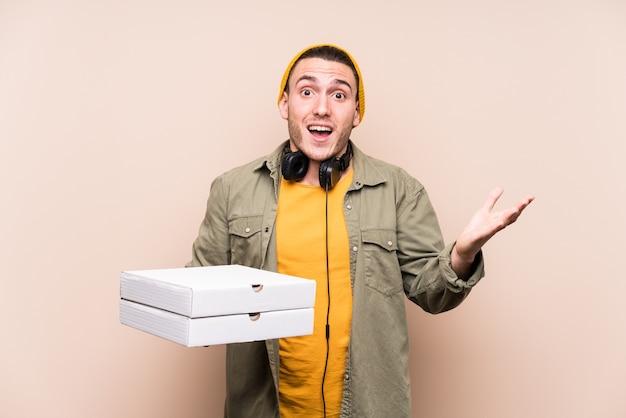 Giovane uomo caucasico tenendo le pizze ricevendo una piacevole sorpresa, eccitato e alzando le mani.
