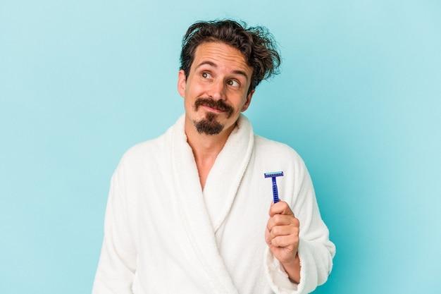 Giovane uomo caucasico che tiene una lama di rasoio isolata su sfondo blu sognando di raggiungere obiettivi e scopi