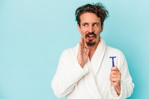 Il giovane uomo caucasico che tiene in mano una lama di rasoio isolata su sfondo blu sta dicendo una notizia segreta di frenata calda e sta guardando da parte